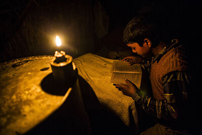 Boy studying in candle light
